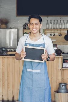 Propriétaire de café masculin asiatique avec tableau blanc