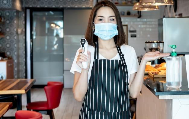 Propriétaire d'un café, portez un masque chirurgical, préparez un désinfectant pour les mains et un thermomètre pour que le client vienne au café