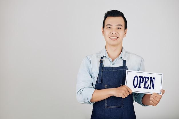 Propriétaire de café tenant une pancarte ouverte