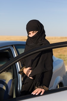 Propriétaire de conducteur de femme islamique à porte ouverte.