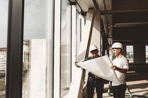 Propriétaire confiant parlant avec son architecte du bâtiment en construction tenant le plan du bâtiment près d'une fenêtre en souriant.