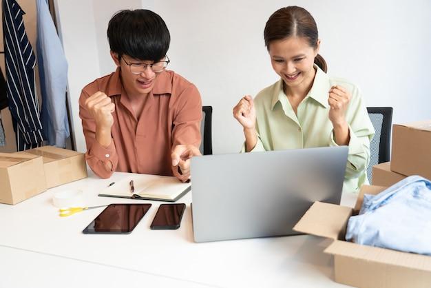 Propriétaire de couple d'affaires asiatique travaillant à la maison avec la boîte d'emballage de leur boutique en ligne se prépare à livrer des produits aux clients, concept de mode de vie de génération alpha.
