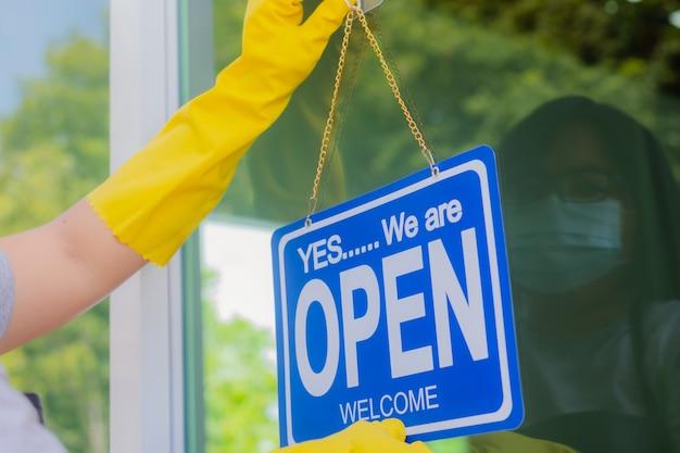 Le propriétaire du magasin accroche une pancarte pour ouvrir un commerce devant la porte.