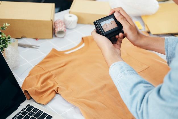 Le propriétaire du vendeur en ligne prend une photo du produit pour le télécharger sur la boutique en ligne du site web