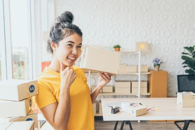 Propriétaire d'entreprise asiatique travaillant à la maison avec boîte d'emballage sur le lieu de travail