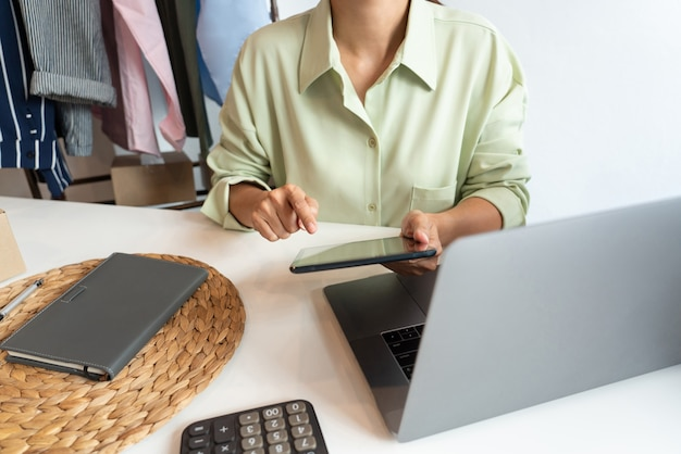Propriétaire d'entreprise asiatique travaillant à la maison avec la boîte d'emballage de sa boutique en ligne se prépare à livrer des produits aux clients, concept de style de vie de génération alpha.