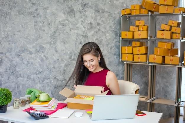 Propriétaire d'entreprise, belle fille qui travaille à la maison et emballer votre commande au client, souriez avec bonheur.