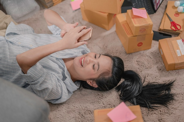 Propriétaire d'entreprise de femmes asiatiques travaillant à domicile avec des boîtes d'emballage au travail elle jouait au téléphone