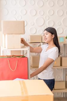 Propriétaire d'entreprise de femmes asiatiques travaillant à la maison avec boîte d'emballage sur le lieu de travail