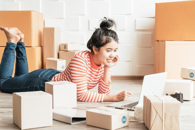 Propriétaire d'entreprise femmes asiatiques travaillant à la maison avec boîte d'emballage sur le lieu de travail
