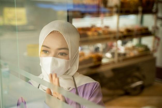 Propriétaire d'entreprise musulmane avec masque en attente de client debout à côté de la fenêtre de son magasin lors de l'ouverture dans la nouvelle normalité