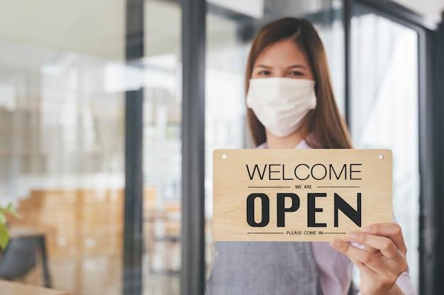 Le propriétaire de l'entreprise ouvre le restaurant comme une nouvelle norme. heureux propriétaire de café café avec masque protecteur tenant une pancarte ouverte en se tenant à la porte du café.