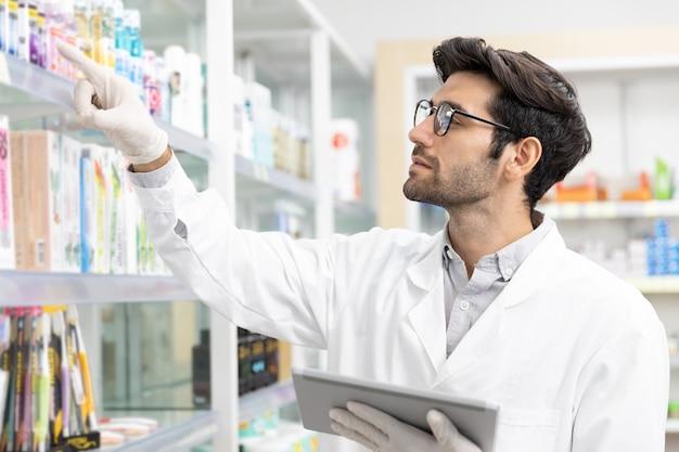 Propriétaire d'entreprise pharmacien masculin du moyen-orient vérifiant la pharmacie de stock à l'aide de la technologie de tablette numérique dans une pharmacie moderne.
