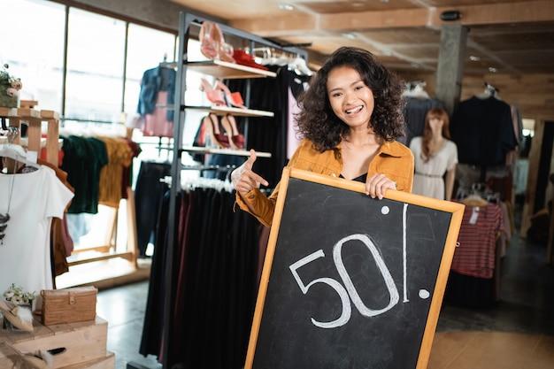 Propriétaire d'entreprise tenant un tableau noir avec 50 pour cent de réduction