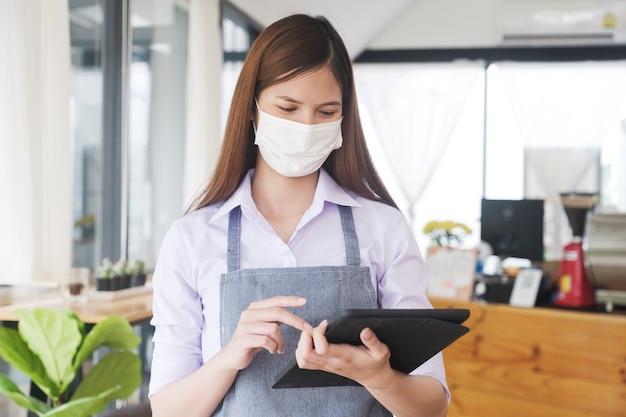 Propriétaire d'entreprise utilisant une tablette pour vérifier la liste en ligne tout en avertissant un masque protecteur.