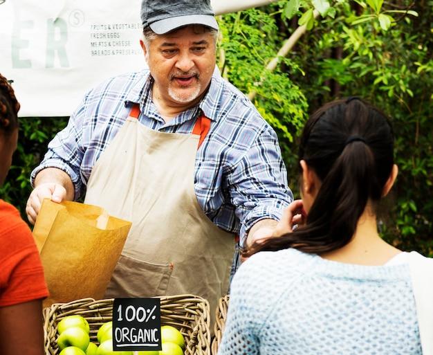 Propriétaire d'épicerie vendant un produit sain au client