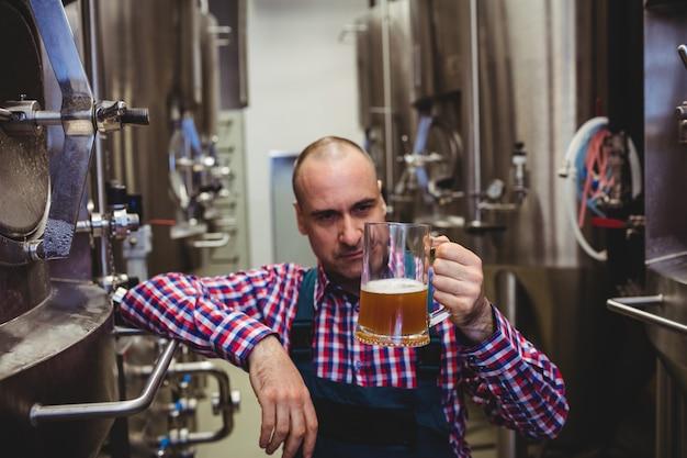 Propriétaire examinant la bière dans une tasse en verre