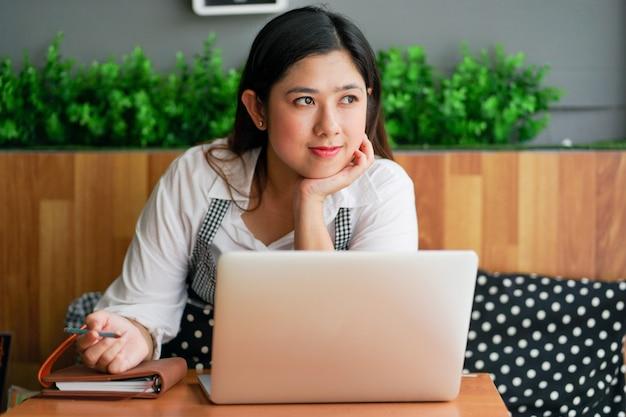 Propriétaire de femme d'affaires à la recherche d'idée ou quelque chose sur ordinateur portable