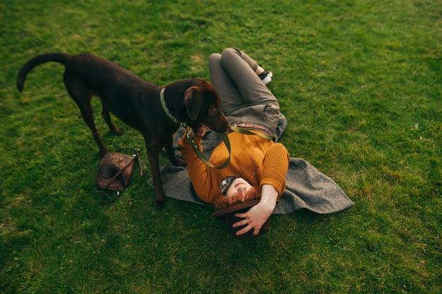 Propriétaire de fille et chien sur pelouse, élégante dame allongée sur l'herbe et tenant le chiot en laisse