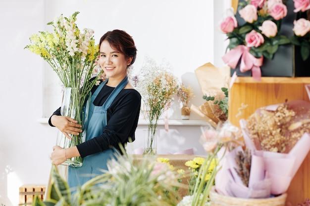 Propriétaire d'un magasin de fleurs enlever un grand vase