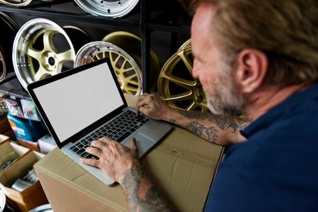 Propriétaire de magasin de pièces de voiture entrepôt vérifiant le concept d'ordinateur portable