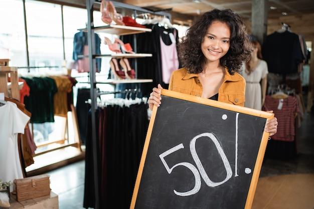 Propriétaire de magasin tenant un tableau noir avec remise