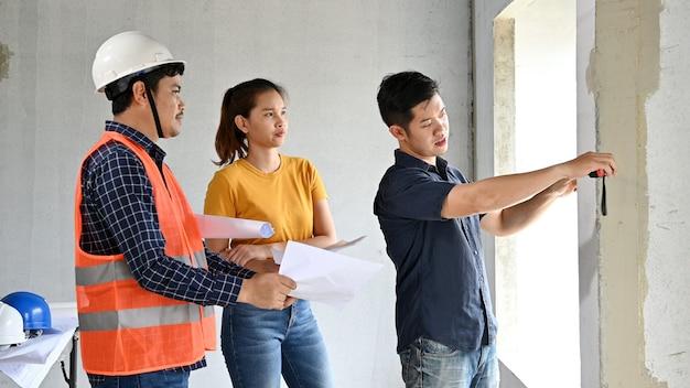 Propriétaire d'une maison neuve inspection avec ingénieur et architecte. couple d'amour au projet de village et à la construction d'un domaine.