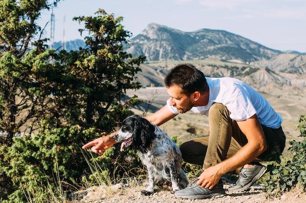 Propriétaire masculin d'un chien épagneul marchant sur fond de montagnes