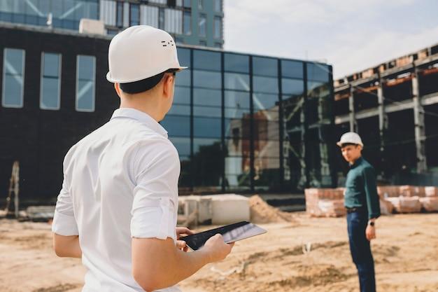 Propriétaire masculin vérifiant comment se déroulent les travaux de rénovation du bâtiment qu'il tient à l'extérieur près du bâtiment.
