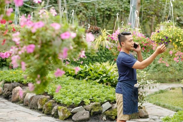 Propriétaire de pépinière de fleurs prenant au téléphone lors de la vérification des fleurs en fleurs sur des pots suspendus