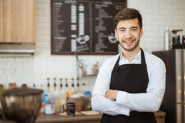 Propriétaire de petit homme d'affaires réussi, debout avec les bras croisés dans un café