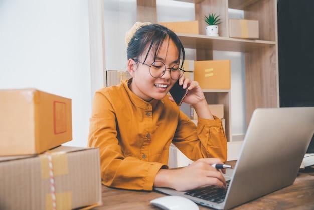 Le propriétaire d'une petite entreprise en ligne prend les commandes des clients en ligne avec plaisir