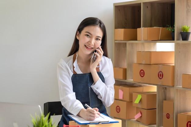 Propriétaire d'une petite entreprise en ligne souriant belle parlant au téléphone. en regardant la caméra.