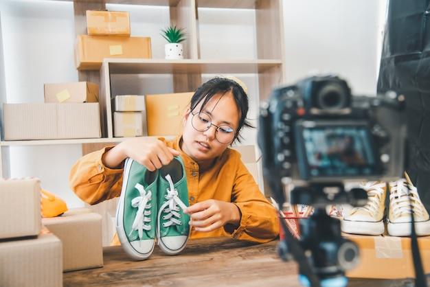 Le propriétaire d'une petite entreprise en ligne travaille en enregistrant des émissions en direct, des critiques de produits et des chaussures d'occasion.