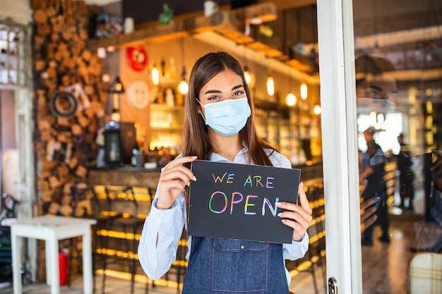 Propriétaire de petite entreprise avec masque facial tenant le signe de la réouverture de l'endroit après la quarantaine