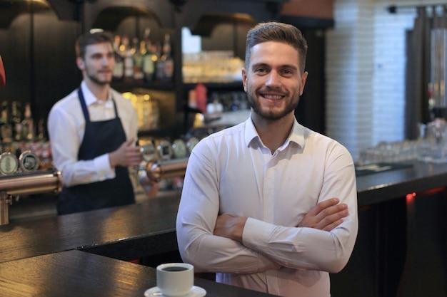 Propriétaire de petite entreprise prospère debout avec les bras croisés avec un employé en arrière-plan préparant le café.