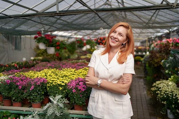 Propriétaire de serre posant avec les bras croisés ayant de nombreuses fleurs et un collègue tenant un pot avec des chrysanthèmes roses sous verrière