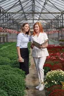 Le propriétaire de la serre présente des options de fleurs à un détaillant client potentiel.