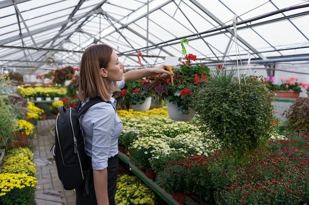 Propriétaire de la serre regardant la récolte des fleurs avec soin
