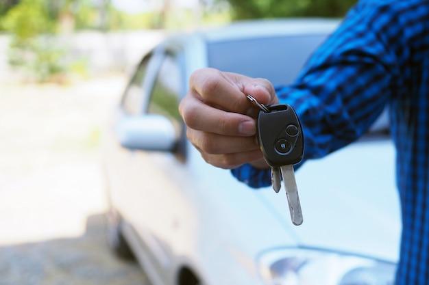 Le propriétaire de la voiture remet les clés de la voiture à l'acheteur.