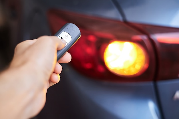 Le propriétaire de la voiture tient dans sa main un dispositif de télécommande pour l'entrée sans clé