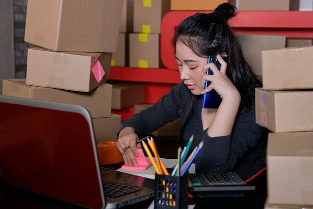 Propriétaires d'entreprise - entrepreneurs de vente en ligne travaillant à domicile recevez les bons de commande des clients avec des emballages, des idées de vente en ligne