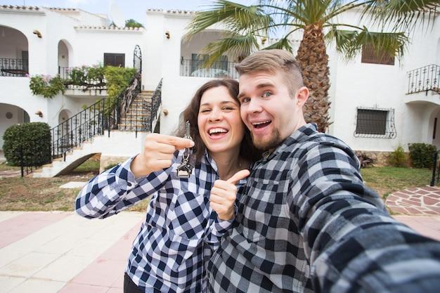 Propriété immobilière et concept d'appartement heureux jeune couple drôle montrant une des clés de leur