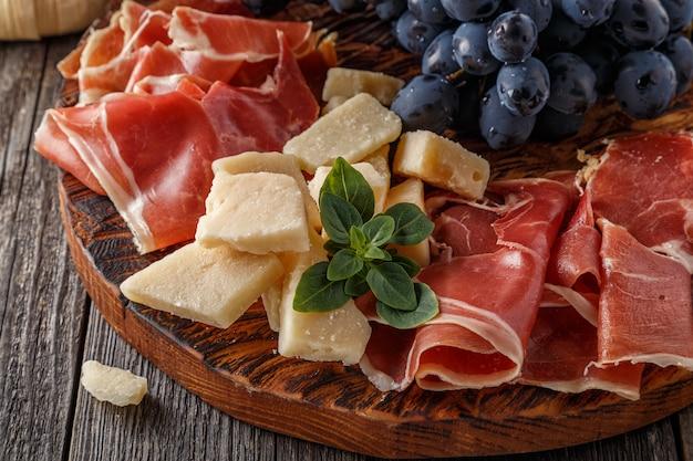 Prosciutto, vin, raisin, parmesan sur table en bois.