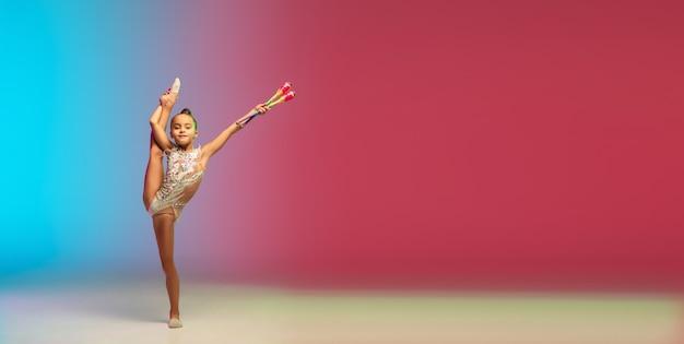 Prospectus. petite fille caucasienne, entraînement de gymnaste rythmique, effectuant isolée sur fond de studio dégradé bleu-rouge en néon. enfant gracieux et flexible, fort. concept de sport, mouvement, action.