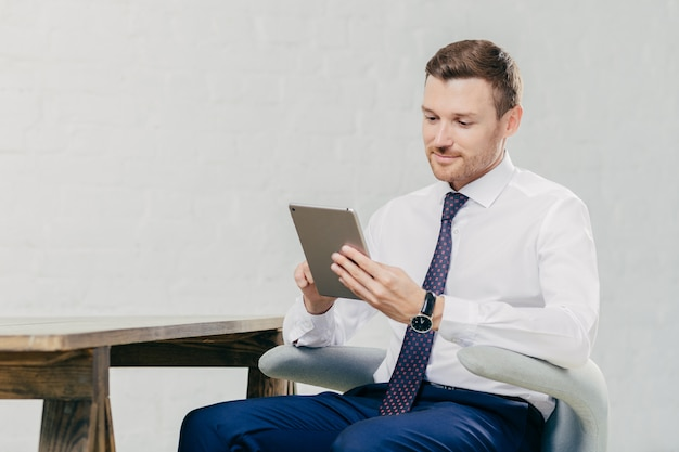 Prospère bel homme regarde webinaire en ligne sur une tablette moderne