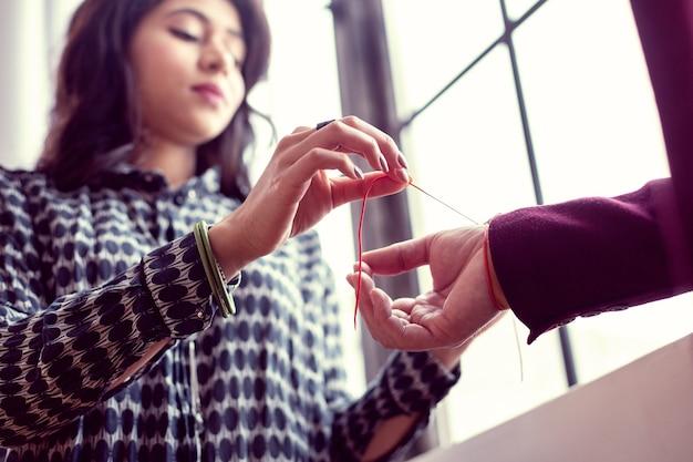 Protection contre le mal. mise au point sélective d'un bracelet rouge spécial mis sur la main pour la protection contre le mal