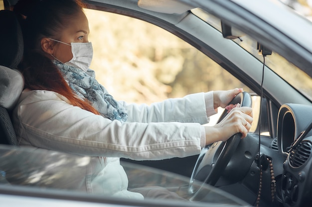 Protection contre les maladies et les coronavirus, une femme dans un masque médical dans la voiture
