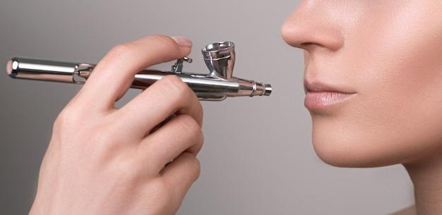 Protection des lèvres. maquillage avec une brosse à air. jeune femme lèvres saines.