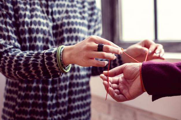 Protection spéciale. mise au point sélective d'un bracelet rouge sur la main masculine tout en étant utilisé pour une protection spéciale
